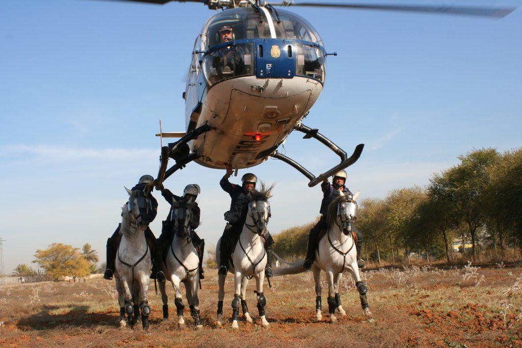 El escuadrón de caballería de la Policía Nacional de Andalucía debajo del helicóptero que rescató los cadáveres de la riada de Badajoz de 1997.